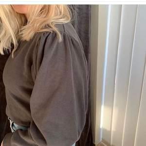 Mörkgrå sweatshirt med detaljer på armarna, knappt använd