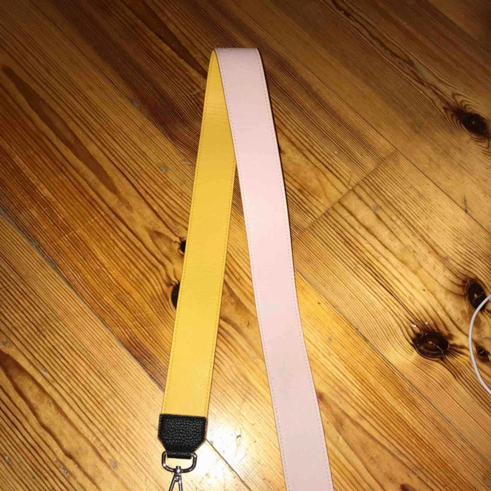 Fint axelremsband från H&M helt oanvänt. Kan vändas till att bara vara rosa eller gult. Väskor.