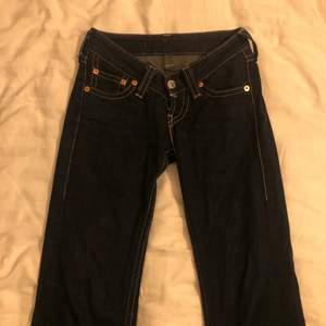 lågmidjade mörkblåa 00s levis jeans som tyvärr blivit försmå. de sitter tajtare vid låten, men mer mot vaden blir de bredare, typ som en bootcut. knappen faller ibland av, men är super enkel att sätta tillbaka på plats igen! jag är 165 och längden var perfekt enligt mig :)