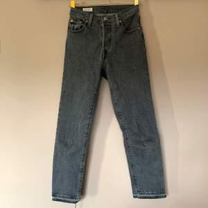 Grå jeans från Levi's, i modellen Cropped 501. Storlek W23/L26. Har sprättat upp sömmen längst ner så de är lite längre och slitna nedtill. Väldigt fint skick!
