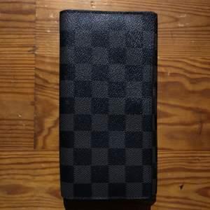 Stor plånbok från Louis vuitton. Har en defekt där lädern är trasig (se sista bilden)