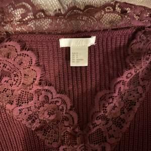 Otroligt fin stockat tröja i vinröd, med spets på v-ringningen, passar till allt möjligt. Så himla finni vintern!