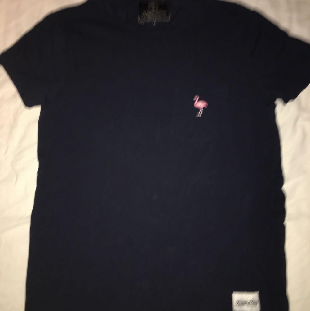 Knappt använd! Stretchigt material👍🏼 en broderad Flamingo på fickan, storlek S! 30kr + frakt 42. Den är mörkblå . T-shirts.