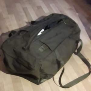 Grön väska av bagmodell. Kan med hjälp av bärremmar som fälls in bakom tygflärpar bäras på ryggen. På ena kortsidan finns en ficka som stängs med dragkedja. Längs hela väskans ovansida sitter en dragkedja för att stänga väskan.LÄNGD 605.0 mm HÖJD 260.0 mm BREDD 375.0 mm
