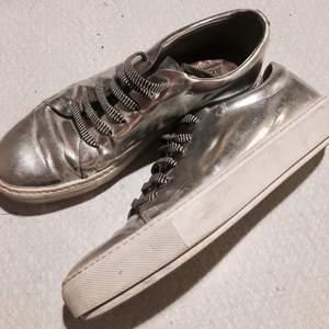 Silvriga sneakers från acne, använt max 5gånger. Medföljer små silvriga plattor med smilies på som man fäster på snörningen, samt vanliga vita skosnören.