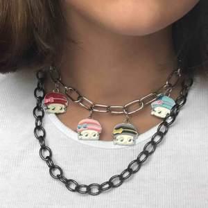 mörkgrå/svart kedja som spänns fast med en säkerhetsnål :) cool att styla med flera halsband!