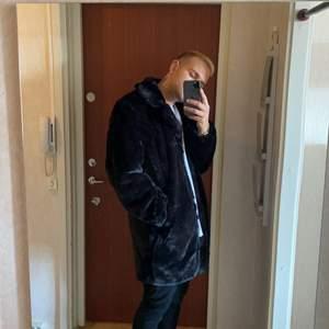 Svart lång jacka i fejk päls. Den är riktigt go att ha över en hoodie och passar extremt bra till både Street stil och mer uppklädd stil. Storleken är Large.