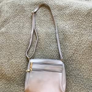 Grå, enkel handväska med gulddetaljer. Finns 2 fack fram och ett bak. Inuti är det ett stort fack och två små fack på sidorna för nycklar och sånt typ:) så inte någon bli ledsen klargör jag att det inte är äkta guld :)