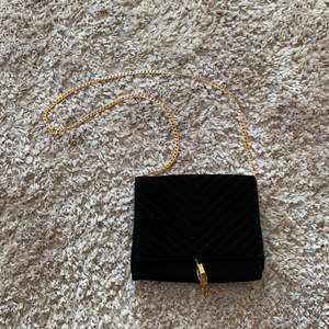 Fin väska från Gina i sammet med gulddetaljer. Bandet går att ha som ett långt eller två kortare. Ett stort fack, två mindre och ett med dragkedja inuti. Frakt ingår ej