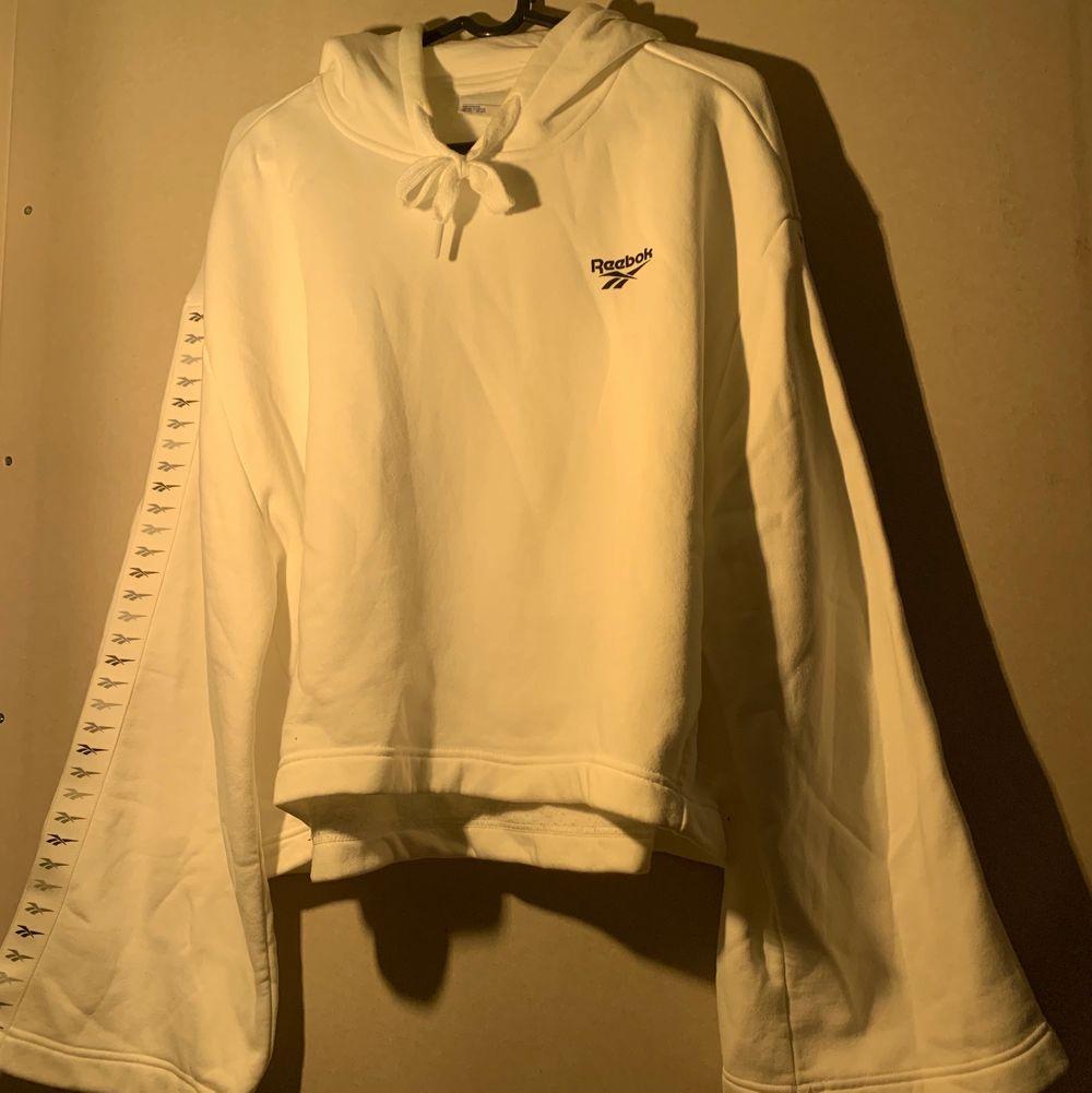 Croppad hoodie från Reebok använd fåtal gånger. Utsvängda fina ärmar. FRI FRAKT!! Nypris- 599kr. Huvtröjor & Träningströjor.
