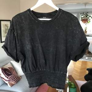 Söt Bershka t-shirt-topp med smock i midjan. Smickrande passform.