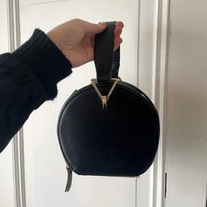 ASSNYGG svart rund väska från MANGO, I HELT NYTT SKICK. Aldrig använd. Den har guldiga detaljer, och är i svart läderimitation. Justerbar då man kan ha den så som i bild men det finns även en band som man kan knäppa på om man önskar.