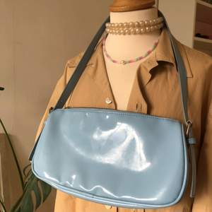 En babyblå vinyl baguettebag köpt från Nelly. Har en fläck (se bild 3)  som inte märks mycket alls om man inte kollar noga. Silvriga detaljer, dragkedja och har en ficka inuti. Skriv för fler bilder eller frågor!!!