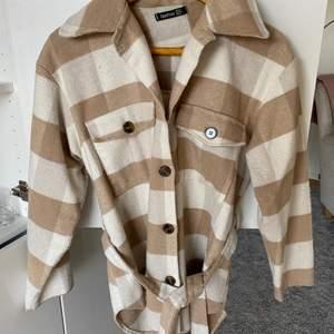 Säljer denna fina kappa med randigt mönster av brunt och vitt. Den är väldigt fin med ett midjeband i midjan för att framhäva. Sjukt fin passform.