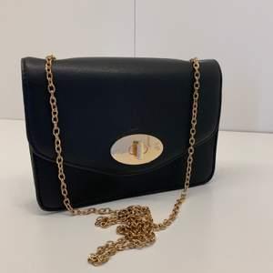 Säljer denna svarta väska. Den är ganska liten men bra att ha om man bara vi ta med sig t.ex. mobil och nycklar. Det är ett guldiga magnetspänne på framsidan som man stänger med och ett guldiga axelband/ kedja. Fint skick, använd ett fåtal gånger. 🌼