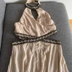 En beige festklänning som endast är använd en gång. Kom dm för hur den sitter på. Storleken är L. Kan mötas upp i Västerås och fraktas.