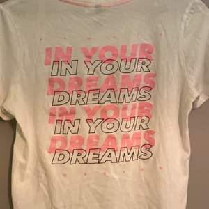 En vit t-shirt med ett stort rosa tryck på ryggen och även ett litet tryck i fram på vänstra bröstet. Köpt på H&M för länge sedan men har ej använt så många gånger så väldigt bra skick. Köparen står för frakt!