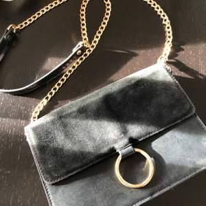Söt axelremsväska i svartrock guld, den är använd och har lite slitningar. Från Nelly