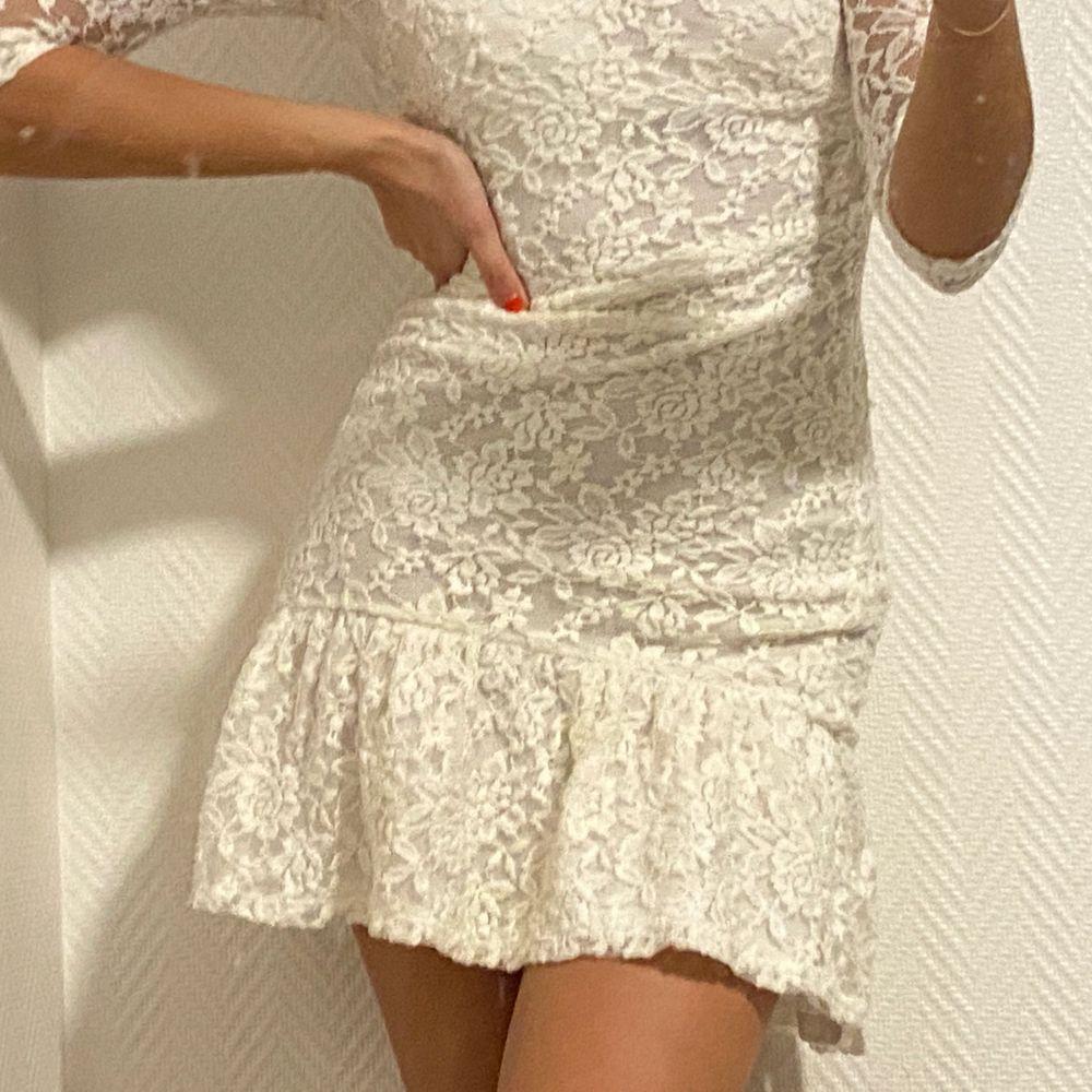 Vit spetsklänning med volang. Klänningar.
