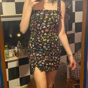 En gullig klänning med blommor på som passar perfekt till både enkla och fina tillfällen, har volanger upptill och sitter perfekt på mig som är 178, är du kortare kommer längden variera men den kommer fortfarande sitta snyggt! Har en slit på ena benet!