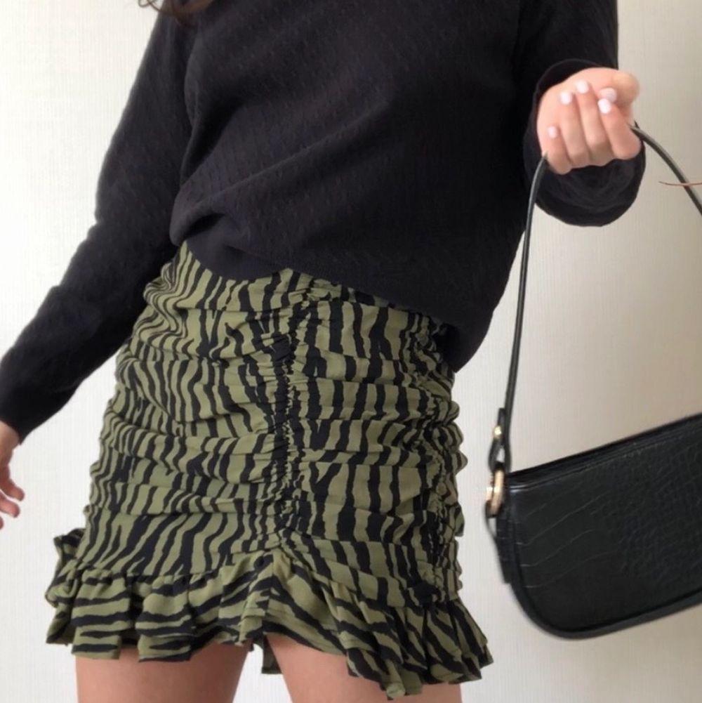Världens finaste kjol som inte går att köpa längre. Den är helt ny med grön och svart mönster, har draperier som formar kroppen, volanger längst med kanten, en dold dragkedja på baksidan och är i M (passform S-M). En asymmetrisk söm vid vänstra låret och en symmetrisk bakom vid rumpan.  Startbud: 100kr exklusive frakt eller köp direkt 400kr exklusive frakt. Ledande bud: 320kr exklusive frakt. Kjolar.