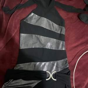 En riktigt fin y2k halterneck med en glimrande detalj vid midjan som man kan se en närmre blick på, på andra bilden. Ganska så stretchig!! Snygg till ett par lågmidjade jeans! Den har tidigare varit en klänning men jag har klippt till den till en tröja! SKRIV PRIVAT VID YTTLIGARE FRÅGOR!