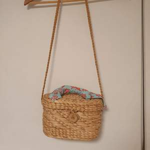 En jättesöt flätad korgväska med tillhörande scarf. Scarfen går att ta av om man inte vill ha den på väskan. Väskan är I princip oanvänd och rymmer mer än man tror och passar jättebra till sommaren. Väskan är enkel att öppna och att stänga.🌺