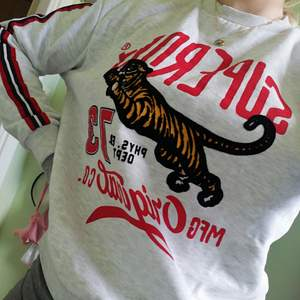 Ljusgrå collegetröja med röd, svarta räverer på ärmarna och stort tryck på framsidan av tröjan, helt ny.