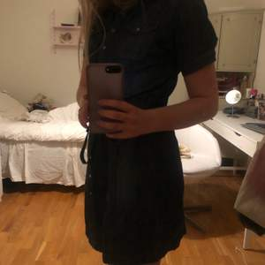 Mörkblå jeansklänning med knappar och knyte i midjan, går ungefär till knäna, stor storlek men passar mig som vanligtsvis har en S utmärkt💙 bara att skriva vid önskan av fler bilder! Köparen står för frakt