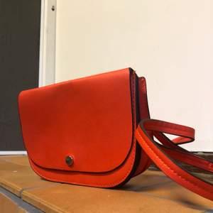 Orange väska i läderimitation. Aldrig använd. Avtagbart axelband. Guld detaljer.