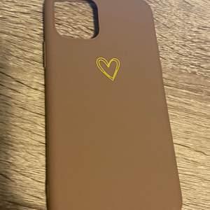 Skal som är brunt med ett guldhjärta i mitten. Säljer då jag råkat köpa till fel mobil