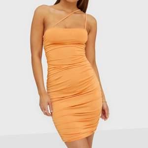 Säljer denhär aprikos färgade Klänningen, den är för liten för mig så har aldrig fått tilfälle att användas. Köpt från Nelly (Nly trend), Storlek XS. Assymetriska axelband