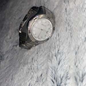 Detta är en silvrig gant klocka som aldrig använts. Klockan har små fina stenar runtom vilket gör den mer stilfull. Jag har tyvärr inget kvitto på klockan men den är köpt i Sverige. Den är vattentålig och rostfri, den är även lite tyngre än vanliga klockor. Batteriet bör bytas ut. STÅR EJ FÖR FRAKT.