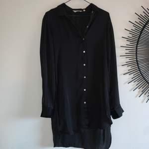 """Svart oversize skjortklänning i silke. Liten """"slits"""" nedtill. Använd 1 gång, bra skick. Storlek xs men är oversize."""