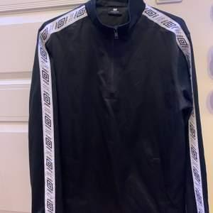Säljer en umbro tröja i lite mer sportigt matrial (se bild) hög i krage men har dragkedja som man kan dra ner. I storlek XS. Använd enstaka gång, kan skickas men köparen står så för frakten!!