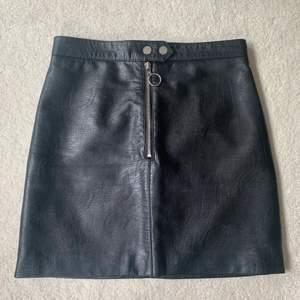 Fin läderkjol (i fakeläder) från Divided i storlek 36. Dragkedja framtil och ser ut som ny!🙂