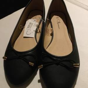 Svarta oanvända ballerinaskor i stl 38 med rosett i fram.  Köpt på skohuset.