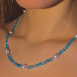 Halsband med vita runda pärlor samt ljusblåa och rosa glaspärlor💙💗🤍                                                               Finns som armband, om du har någon annan design som du skulle vilja ha så går det oftast att fixa - pärlkombination, mönster, färg mm🌟 Kolla min profil för fler smycken