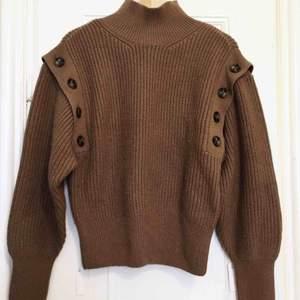 Trendig stickad tröja i skön ullblandning. Ärmarna kan knäppas av så får du en väst!   Skriv gärna vid frågor!