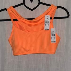Oanvänd orange bikini i strl 36. Överdelen känns mer som strl 34