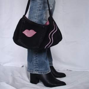 Handväska i baguettebag stuk gjord i svart jeans med en ytterficka och innerficka som har dragkedja. Insidan är i rosa som matchar applikationer. Helt handsydd, fler bilder på insta @avpermert
