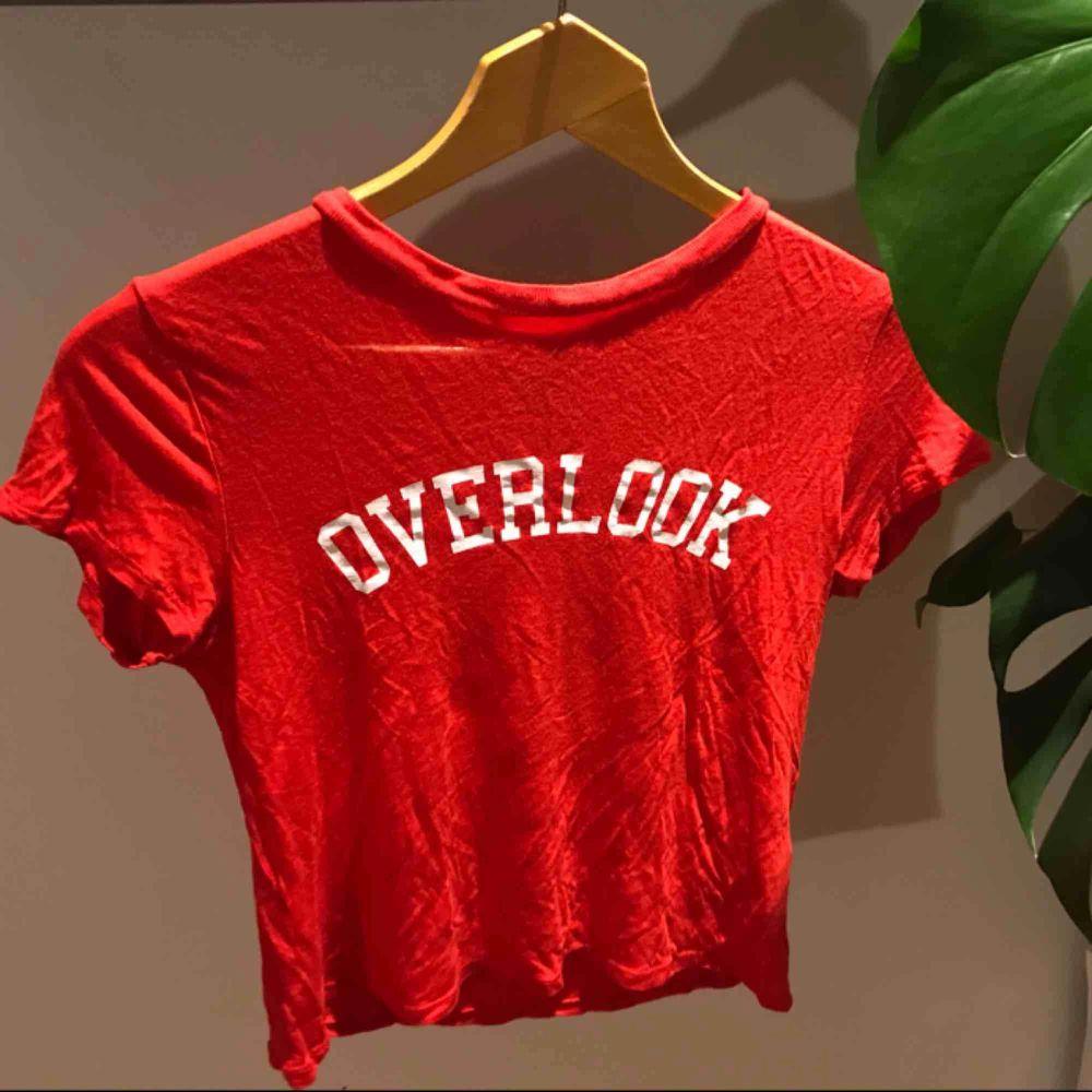 """Jättefin klarröd t-shirt från H&M aldrig använd då den inte kommit till användning. Med tryckt text """"overlook"""" Bra till sommaren och varmare väder! Frakt tillkommer :). T-shirts."""