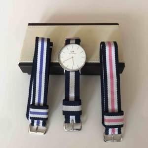 Tre Daniel Wellington armband och klockan. Allt har silverdetaljer. Blått, lila och rosa armband. Klockan går självklart att flytta till önskat band. 36mm på alla band. Använda men inte slitna.