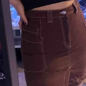 Mörkbrun kjol med vita sömmar från weekday i jeans material. Säljer så den är för liten:( köpare står för frakt🥰