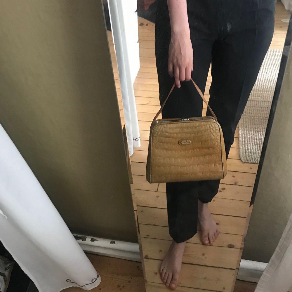 Gul vintage mellanstor väska. Platt och stabil botten vilket gör väskan väldigt rymlig. Kort handtag och guldiga detaljer och knäppe. Aldrig använd. Frakt tillkommer. . Väskor.