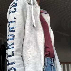 En snygg Superdry hoodie i mycket bra skick. Den blå paljet text på ena ärmen och vid bröstet på motsatt sidan. Säljer pga att den är för liten. Köparen står för frakten❤️