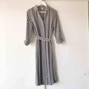 Underbar klänning ifrån H&M i färgerna svart/vit med gulddetaljer.  Avtagbart och reglerbart skärp. Passar en 36/38. Fantastiskt nyskick, använd en gång!  Ordinarie pris: 399kr