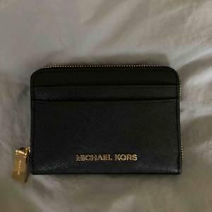 Svart Plånbok med guld detaljer! Köpt på Michael Kors butiken för 1100kr! 11 cm bred x 9 cm hög Hör av för fler bilder! Den är såklart äkta, ska leta upp kvittot! Säljer då den aldrig kommit till användning för min del! Fraktar ej!  Möts upp i Stockholm!