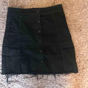 Svart jeanskjol med knappar, passar 32-36 stretchiga.