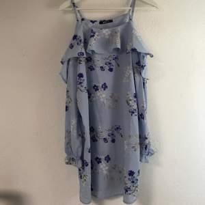 Söt och somrig ljusblå cold-shoulder klänning med blommor. Är i storlek 36 men passar 38 och kanske även 40 pga den vida passformen. Jättefin klänning som bara användts till en skolavslutning och sedan bara hängt i garderoben. Inköpt för ca 299kr på Gina tricot men säljs för 110kr  inklusive frakt! Skriv vid intresse!!